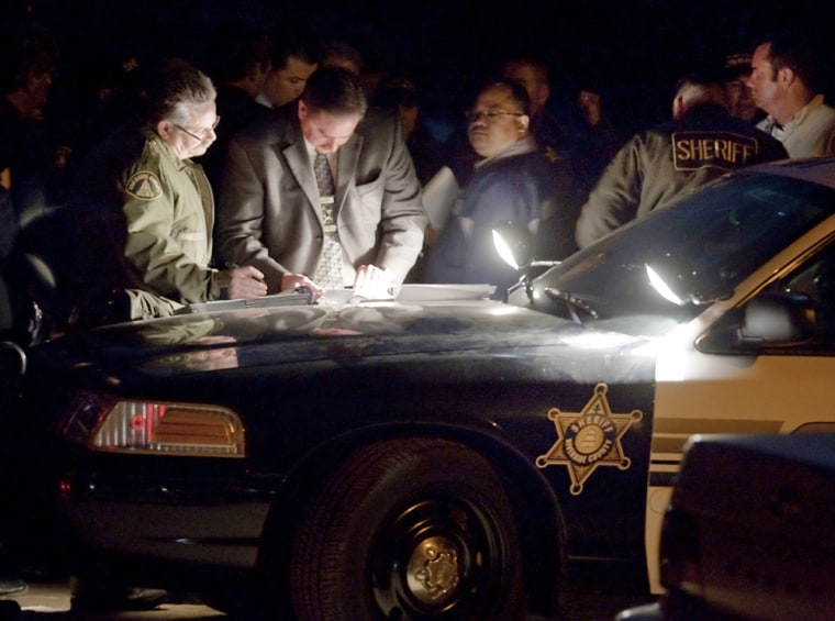Image: Investigators use lights from a Riverside Sheriff's car to hold a meeting
