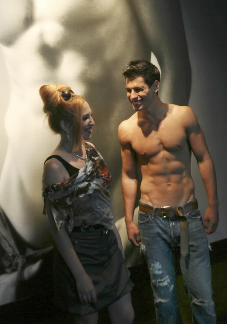 Amale model greets a shopper at Abercrombie & Fitch in New York. Will this approach work in a downturn?
