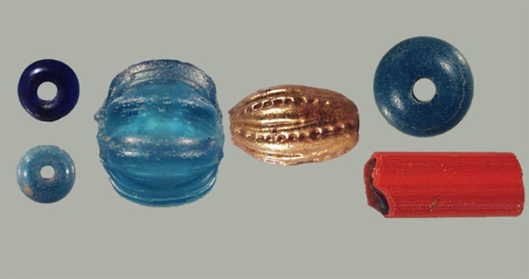 Beads from the excavation of the Santa Catalina de Guale Mission on St. Catherines Island off Georgia. From left to right: On top: Common cobalt blue seed bead, most likely from Venice (20,906 found); bottom: Venetian turquoise/green-blue seed bead or rocaille (5777 found); unique blue green melon bead from China; Spanish gilded oval glass bead (15 found); On top: Ichtucknee plain turquoise blue bead with white patinas now thought to be manufactured in France (one of 5,265); bottom: Green Heart bugle bead with a thin clear veneer over red-orange glass over green glass from the Margariteri guild of Venice (one of 5). Credit: AMNH