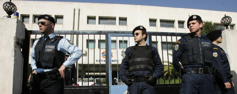 Police stand outside a state vocational training college in western Athens, Greece, where a 18-year-old student shot and injured a fellow student and two passers-by before fatally shooting himself in the head, on Friday.