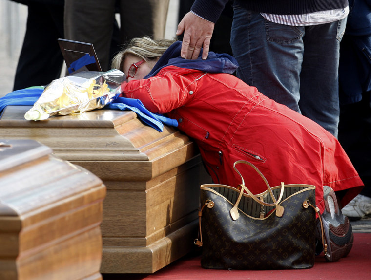 Image: A woman kneels over a coffin