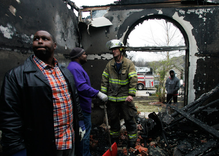 Image: Nathan Christmon, left, surveys the damage to his home in Midwest City, Okla