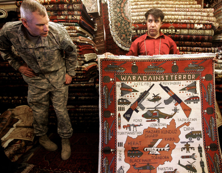 """Zulmai, an Afghan Carpet seller, displays his """"war rug"""" featuring a variety of weapons to Army Lt. Col. Chris Kubik at his shop in Camp Eggers, the U.S. base in Kabul, Afghanistan, Thursday, March 12."""