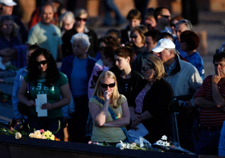 People gather to look at the plaques for the 13 victims of the massacre at Columbine High School after a service to mark the 10th anniversary of the school killings in Littleton, Colo., on Monday.