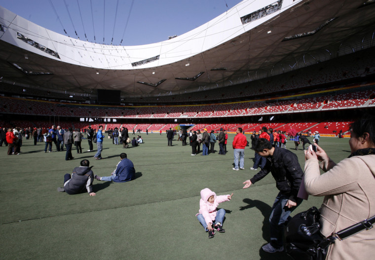 Image: Tourists walk and take photographs on the infield of the National Stadium
