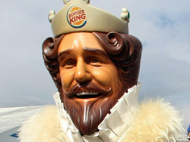 The Burger King mascot  stands outside t