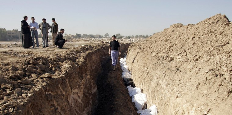 Image: Bodies are laid to rest in a mass grave in the north eastern town of Baquba