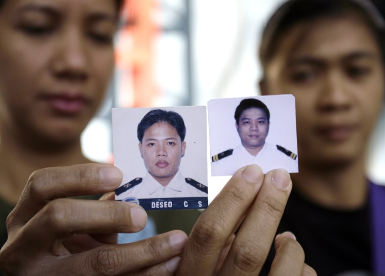 Image: Families of hostages show their photos.