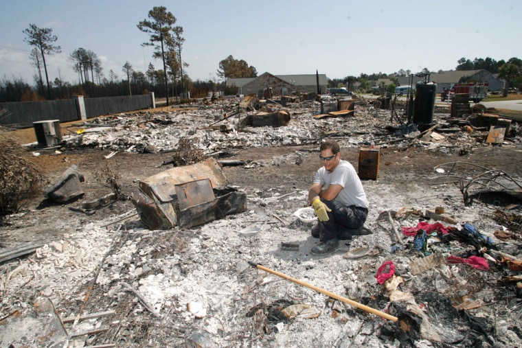 Adam Cumbo sifts through the rubble in search for his mother-in-law's class ring in what used to be his in-laws house on Saturday in North Myrtle Beach, S.C.