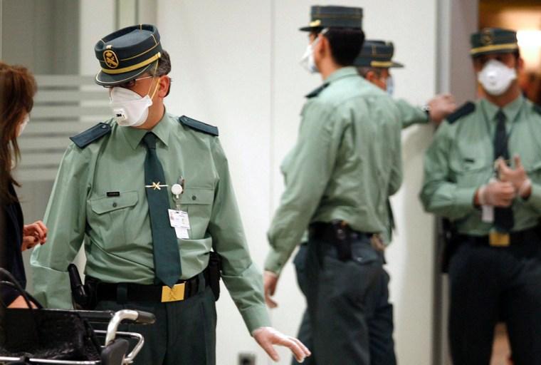 Image: Guardia Civil members wear face masks at Barajas international airport