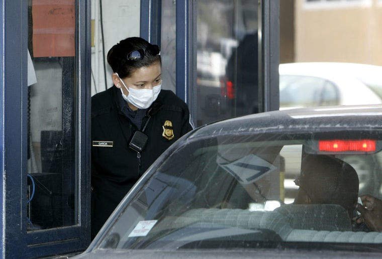 Image: Customs and Border Protection agent wears a protective mask