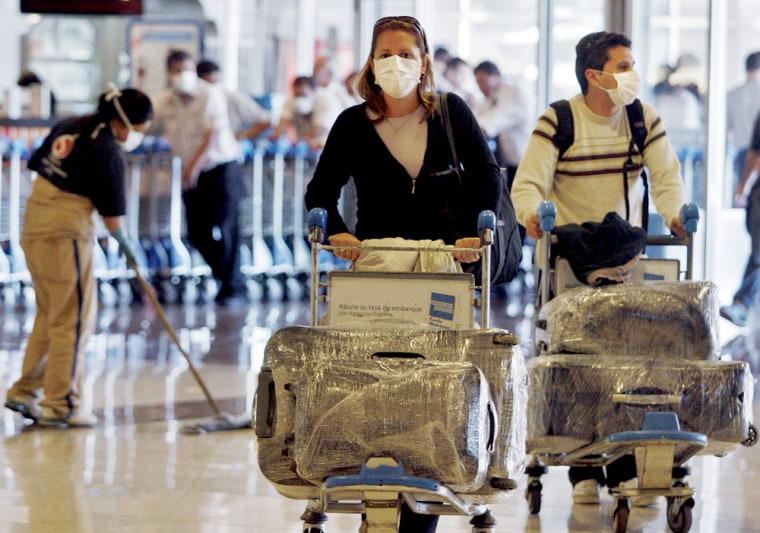 Image: Passengers wearing protective masks arrive at Buenos Aires' airport