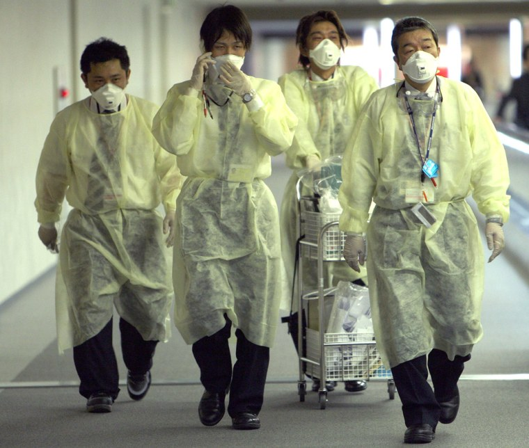Image: Quarantine officers walk to airplanes arriving from Mexico