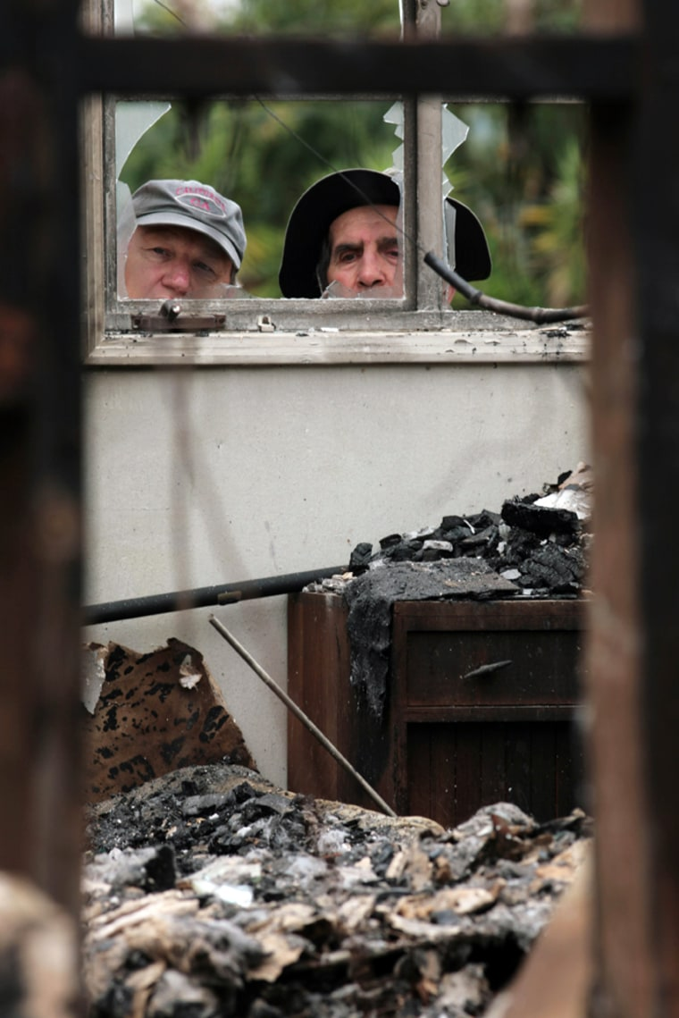 Roger Jacobson, left, and his father-in-law, Robert Pratini, peer into the bedroom of Pratini's burned home in Santa Barbara, Calif., on Sunday.