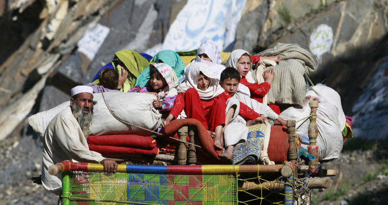 Image: Family fleeing military operations in Swat valley sit with their belongings on back of truck in Malakand district