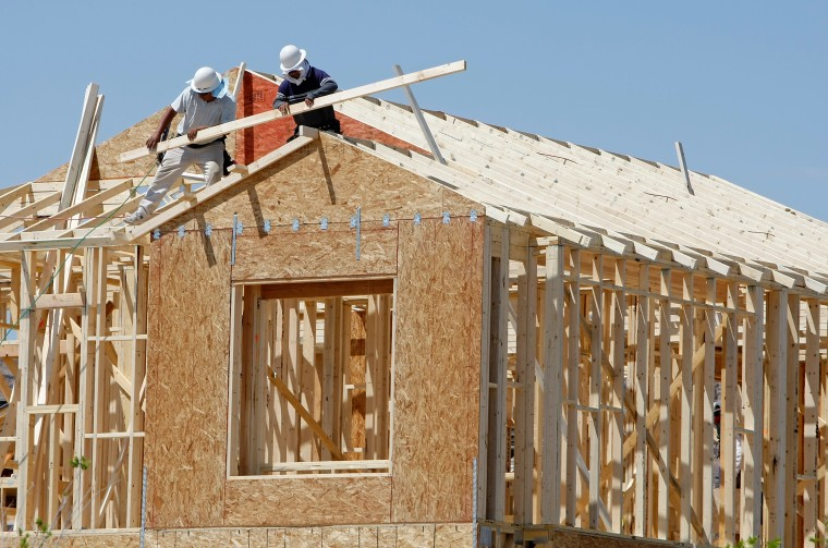 Image: Construction workers build a house