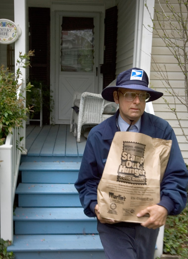 Mail carrier Scott Smith collects donated food from a home on Beardsley Avenue in Elkhart as part of the National Association of Letter Carriers Food Driveon May 9.