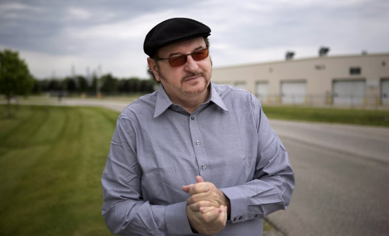 With the shuttered Monaco motorhome factory behind him, Wil Cashen stands alongthe industrialcorridor in Wakarusa, Ind., thathe envisions as the center of an electric vehicle industry.