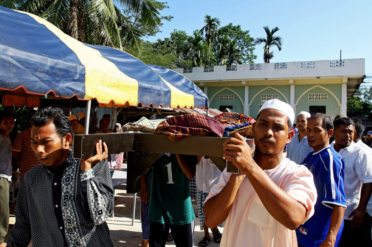 Image: Thai Muslim villagers remove a victim's body from a mosque