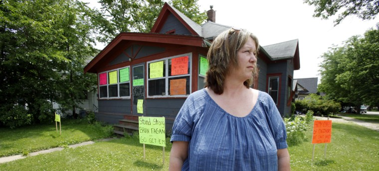 Image: Jaylynn Banks stands in front of her old home which flooded a year ago in Cedar Rapids, Iowa.
