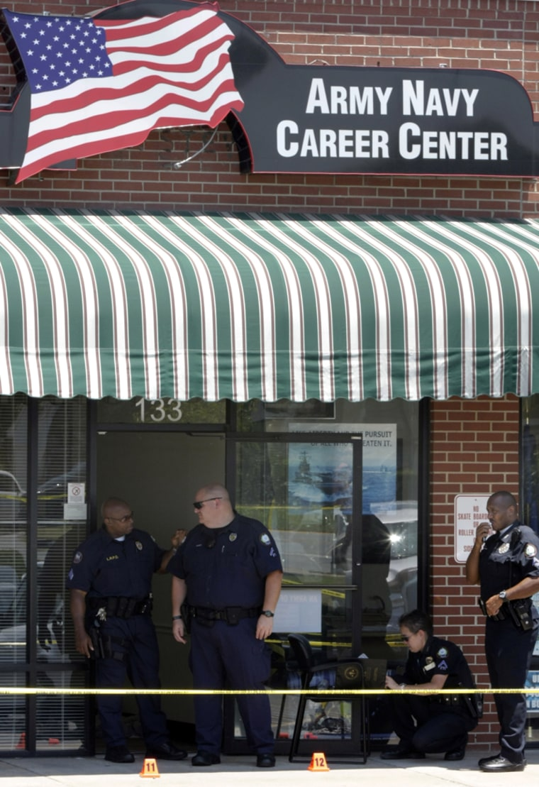 Image: police inspect the scene of a shooting outside a military recruitment office in Arkansas