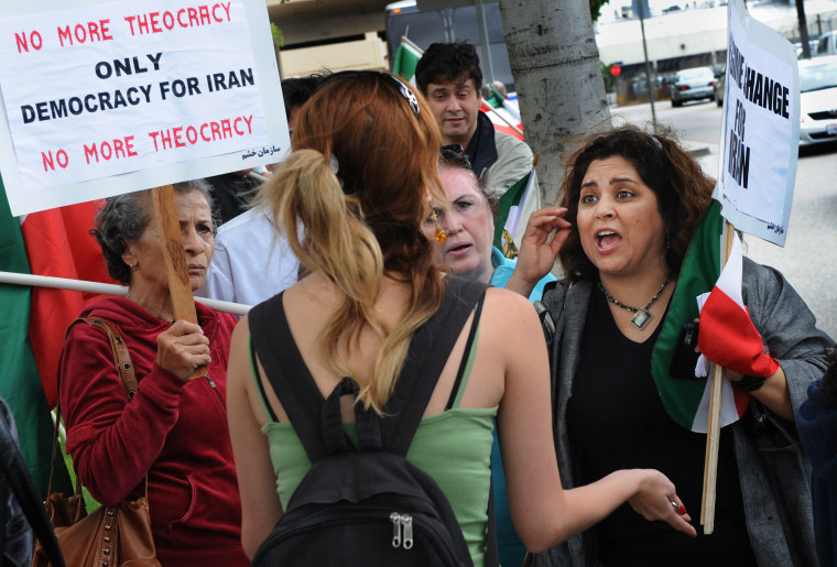 Image: An Iranian woman (C) who has just voted, argues with members of a group protesting against the Presidential elections in Iran, outside a polling booth for the local Iranian community in Los Angeles