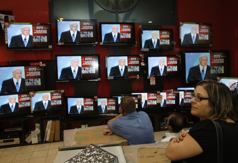 Image: Israeli shopper stands in front of televisions broadcasting the speech of Israel's PM Netanyahu in Jerusalem