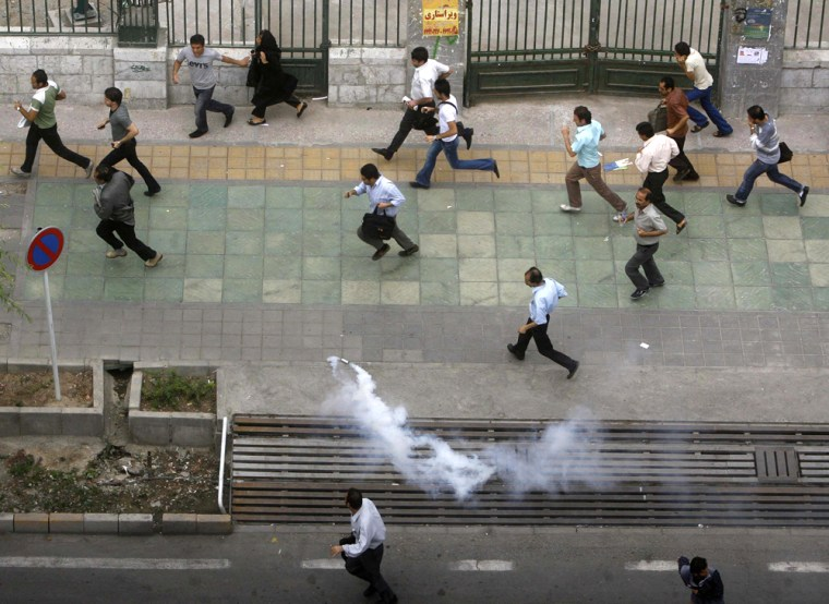 Image: Iranian demonstrators run for cover as policemen use tear gas