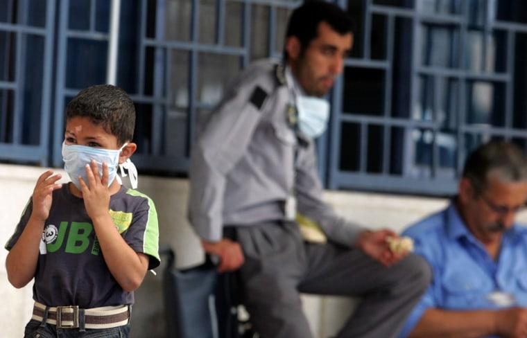 Image: Jordanian boy puts on his mask in Amman, Jordan