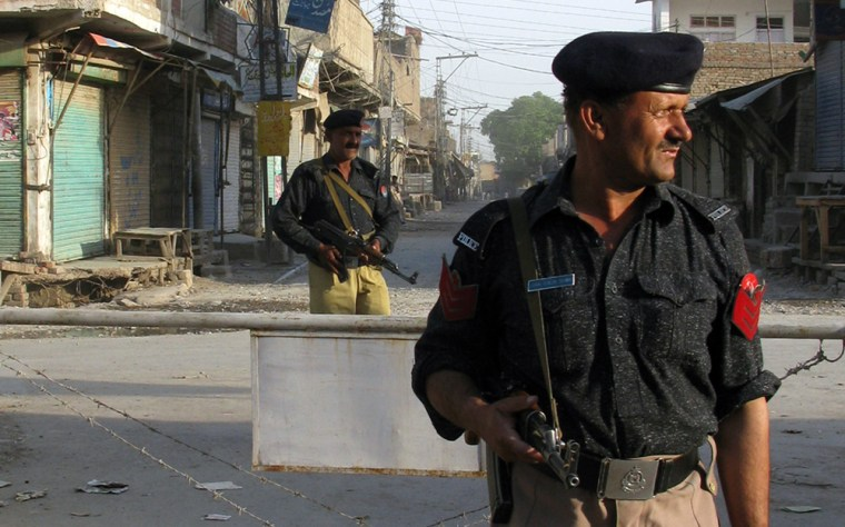 Image: Pakistani policemen stand guard on the streets during a curfew in Bannu