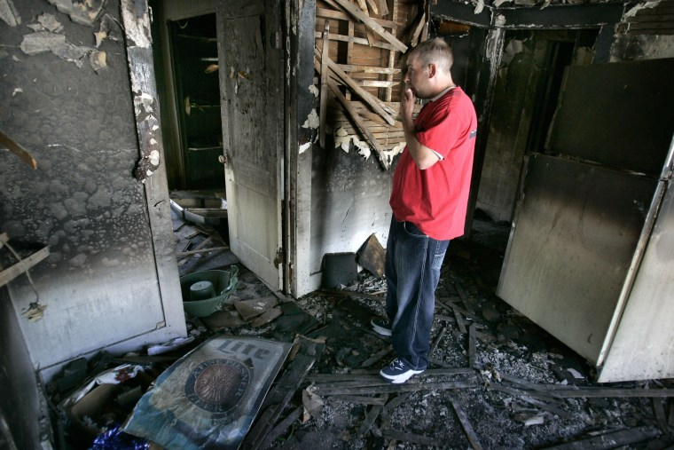 Image: Elmer Crawley, Gordy Yoesting's half-brother, looks over the burned remains of the home in Flint, Mich.