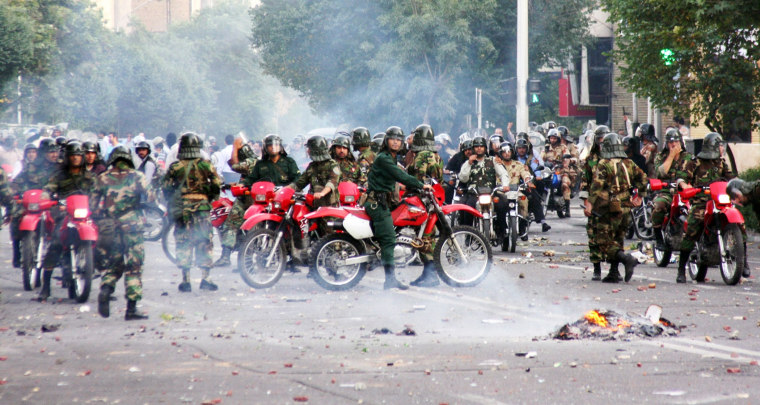 Image: Iranian police sit on motorcycles as they face protesters during a demonstration in Tehran