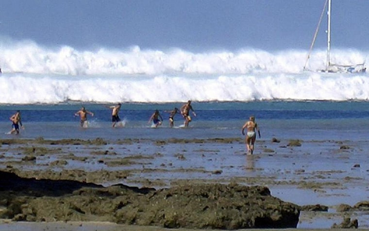 Image:  Tourists caught run from a wave caused by a tsunami at Hat Rai Lay Beach, near Krabi in southern Thailand.
