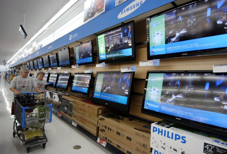 Image: Shoppers walk past televisions on display in the electronics department of a Wal-Mart store in Rogers, Ark.