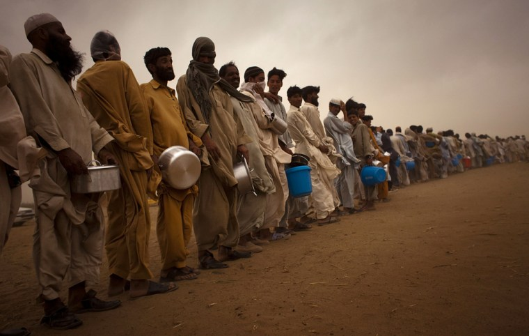Image: Displaced people line up at the Chota Lahore refugee camp