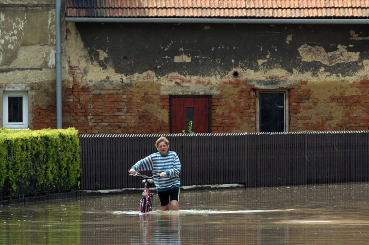 Image:A woman pushes her bicycle through a flooded street