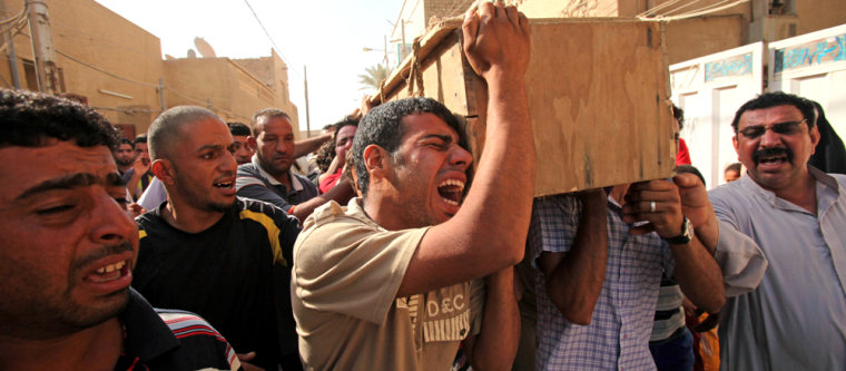 Image: Men carry the coffin of a relative killed in a bombing in the main Shiite district in Baghdad.