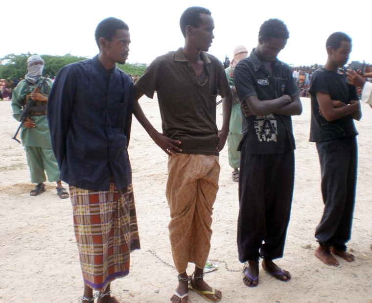 Image: Four men sentenced to have a hand and foot cut off   stand in a  square in north of Mogadishu, Somalia