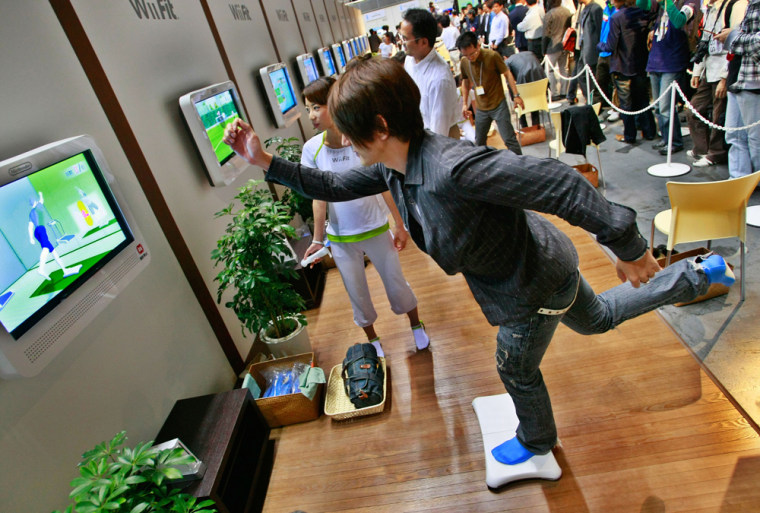 """Image: A model demonstrates Nintendo Co.'s game \""""Wii Fit\"""""""
