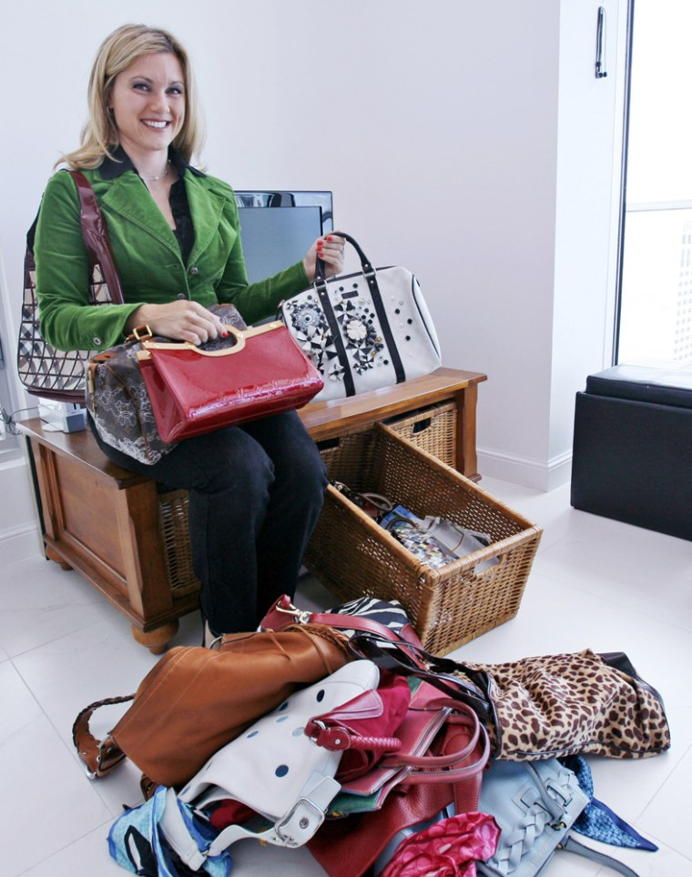Image: Cassandra Smith holds four designer handbags that she rents as she poses with a pile of handbags on the floor that she bought in her pre-rental days.