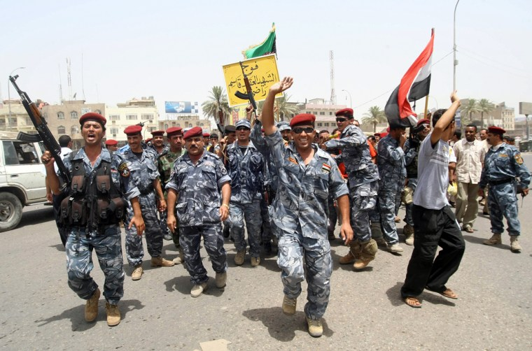 Image: Iraqis police and soldiers celebrate on the streets of the southern city of Basra