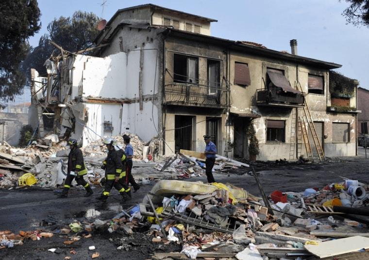 Image: Rescuers walk by the rubble of a collapsed house in Viareggio