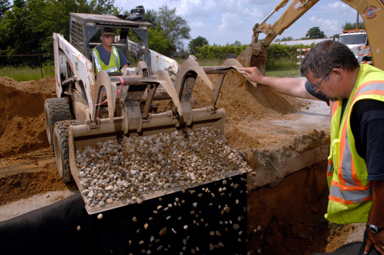Image: City workers backfill a ditch with stones after installing new drainage pipes.