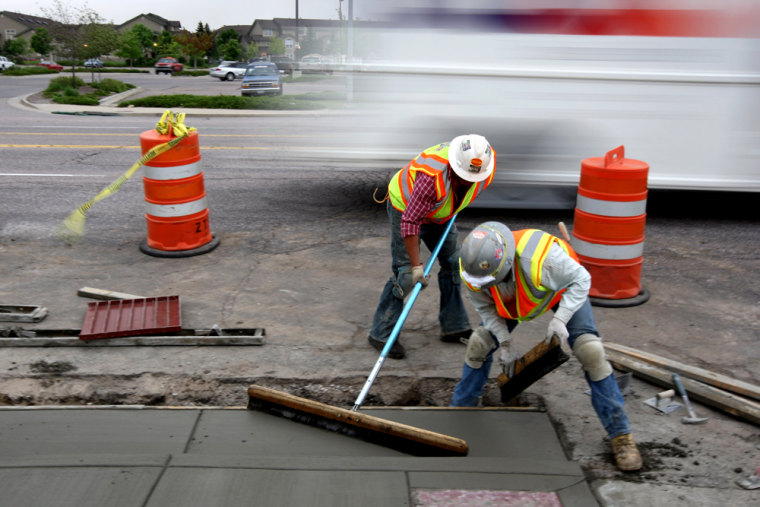 Image: Workers smooth out a new sidewalk at a federal stimulus funded road project in Colorado