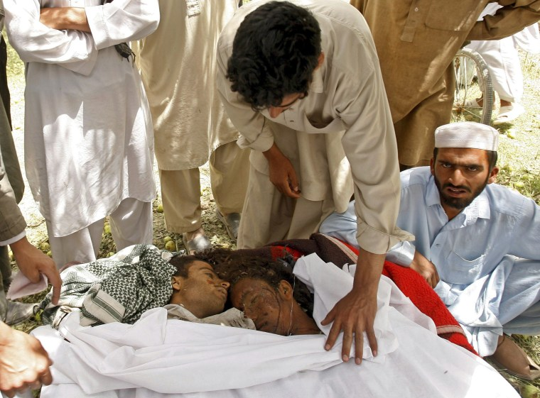 Image: Afghan men inspect the bodies of victims at the site of an explosion in Logar province south of Kabul