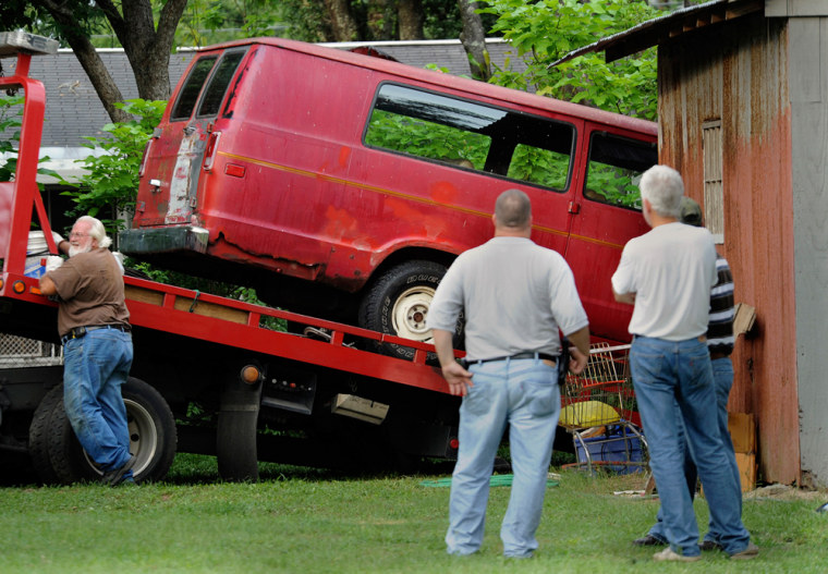 Image: Escambia County Florida law enforcement personnel watch as a van is removed from behind a shed where it was discovered Saturday evening