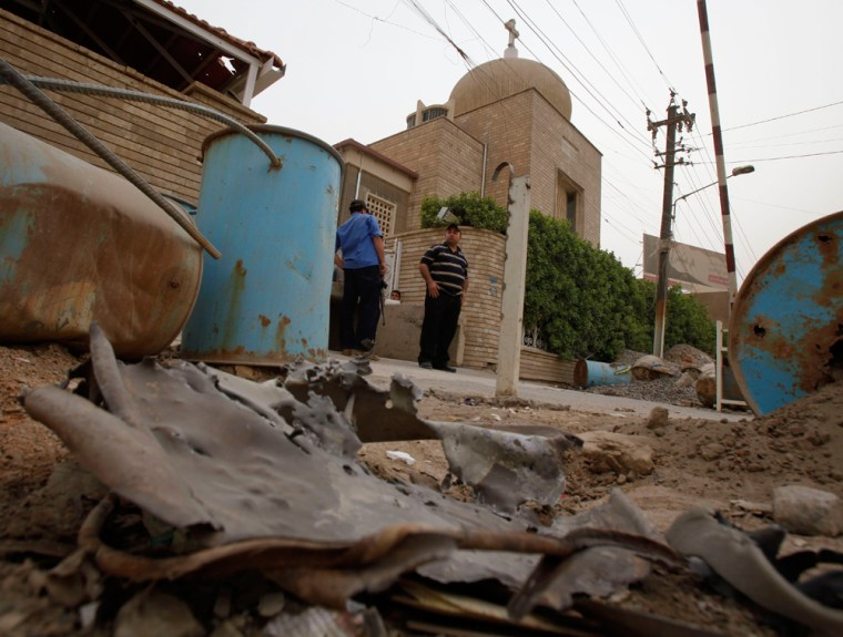 Image: Iraqi security forces stand guard outside one of several Christian churches that were bombed in Baghdad, Iraq