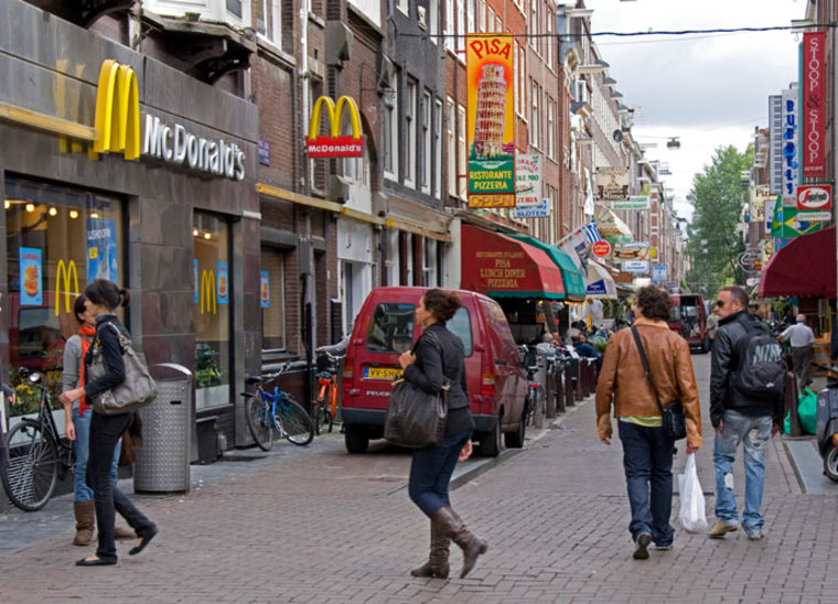 Active Amsterdam street with many people walking past McDonalds and a pizza parlor