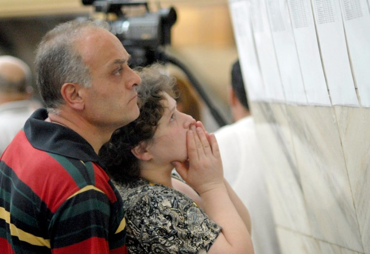Image: Relatives look through the list of passengers