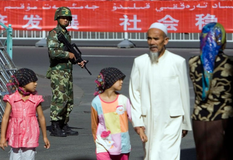 Security forces stand guard in a predominantly ethnic Uighur area in Urumqi as an Uighur family passes by